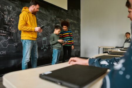 Center For Excellence. Young male science teacher standing near the blackboard, holding tablet pc and looking at his students while they are demonstrating their own robot vehicle