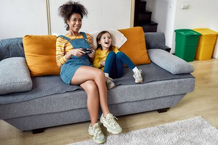We make baby care easy. African american woman, baby sitter and caucasian cute little girl having fun together, playing video games, sitting on the couch. Leisure activities, babysitting concept Imagens