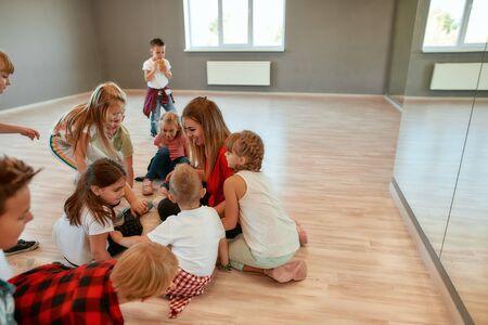Spending time with kids. Full length portrait of positive dance teacher talking to group of little girls and boys sitting on the floor in studio