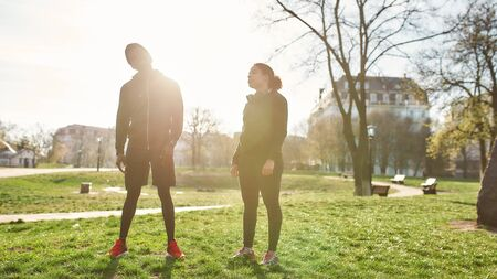 Sporty african couple exercising in the morning outdoors. Full length of dark skinned man and woman in black sportswear working out in park