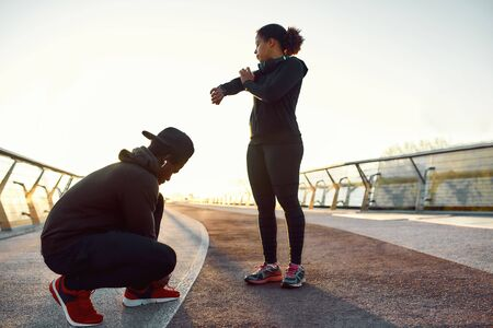 Active young african couple, man and woman in sport clothing tying shoelaces, preparing before jogging outdoors. Morning cardio 스톡 콘텐츠