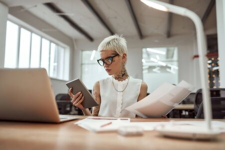 Making business easier. Young and beautiful tattooed business woman wearing glasses working with digital tablet while sitting at her workplace in the office