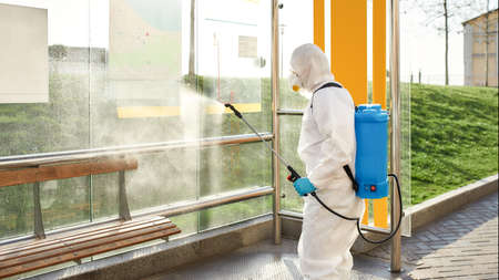 No germs allowed. Sanitization, cleaning and disinfection of the city due to the emergence of the Covid19 virus. Man in protective suit and mask at work near the bus stop