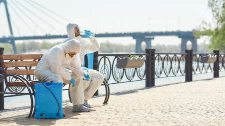 Exhausted. Sanitization, cleaning and disinfection of the city due to the emergence of the Covid19 virus. Specialized team in protective suits and masks takes a break near the riverside
