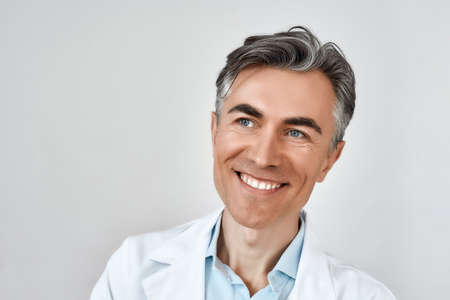 Close up portrait of senior cheerful male doctor smiling while posing against grey background in studio. Headshot