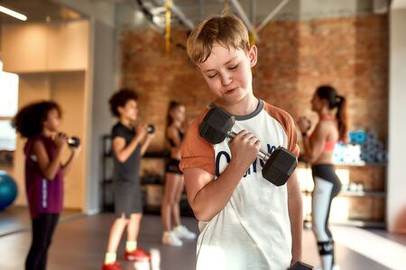 Caucasian boy smiling while exercising using dumbbell in gym together with female trainer and other kids. Sport, healthy lifestyle, physical education concept Reklamní fotografie