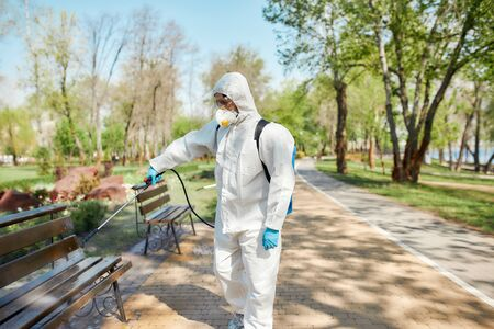 Service you can trust. Sanitization, cleaning and disinfection of the city park due to the emergence of the Covid19 virus. Worker in protective suit and mask