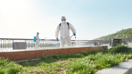 Simplifying Life. Sanitization, cleaning and disinfection of the city due to the emergence of the Covid19 virus. Specialized team in protective suits and masks at work near the riverside