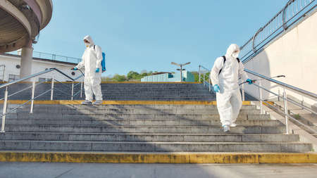 Stop spreading germs. Sanitization, cleaning and disinfection of the city due to the emergence of the Covid19 virus. Specialized team in protective suits and masks at work