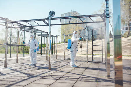Safety is our Priority. Sanitization, cleaning and disinfection of the city due to the emergence of the Covid19 virus. Specialized team in protective suits and masks at work near sports ground