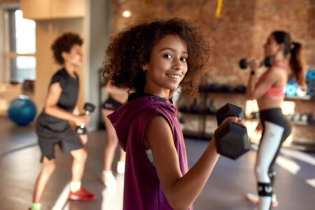 African american girl smiling at camera while exercising using dumbbell in gym together with female trainer and other kids. Sport, healthy lifestyle, physical education concept Reklamní fotografie