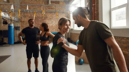 Group of sportive people in black sportswear standing at industrial gym. Man and woman trying arm wrestilng playfully. Group training, teamwork concept