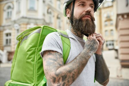 Close up of brutal bearded delivery man wearing helmet while standing with thermo bag or backpack outdoors, ready to ride a bicycle. Courier, delivery service concept