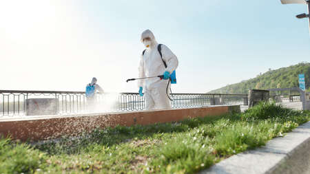 Make your change for good. Sanitization, cleaning and disinfection of the city due to the emergence of the Covid19 virus. Specialized team in protective suits and masks at work near the riverside