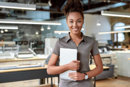 You are unstoppable if you have a strong vision. Attractive african american worker standing in office