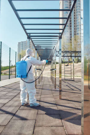 Professional Service. Sanitization, cleaning and disinfection of the city due to the emergence of the Covid19 virus. Man in protective suit and mask at work near sports ground