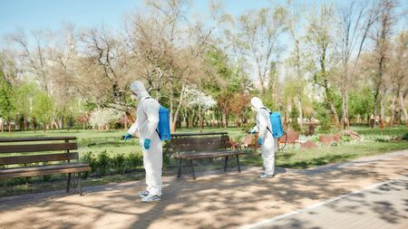 Clean City. Sanitization, cleaning and disinfection of the city park due to the emergence of the Covid19 virus. Specialized team in protective suits and masks at work