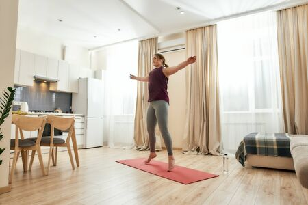 Full length shot of young curvy woman in sportswear exercising on a yoga mat at home. Determination, will power, sport concept. Horizontal shot