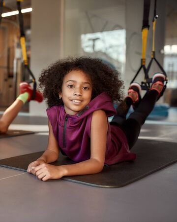 Teenage girl looking at camera while doing exercises on mat using fitness straps in gym