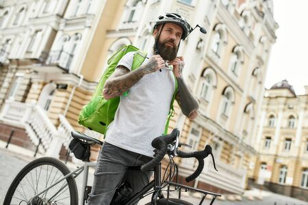 Hot and fast. Brutal bearded delivery man wearing helmet, looking aside while standing with his bicycle outdoors, ready to work. Courier, delivery service concept