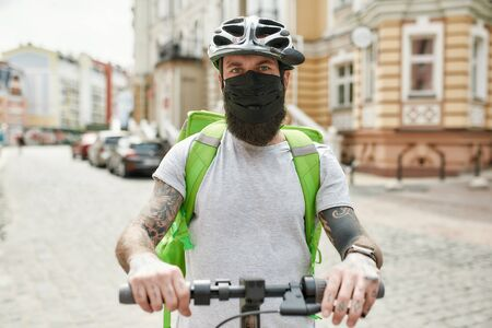 Brutal bearded delivery man in helmet wearing mask due to the emergence of the Covid19 virus, riding a scooter, delivering food. Main focus on a man, blurred background. Courier, delivery service
