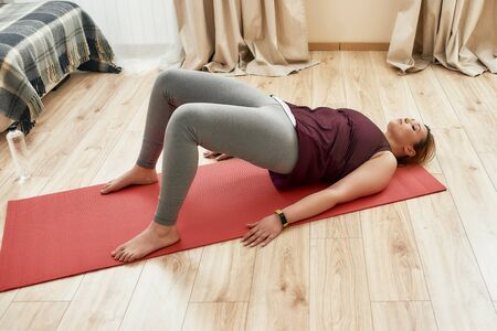 Do more. Full length shot of young curvy woman in sportswear exercising on a yoga mat at home