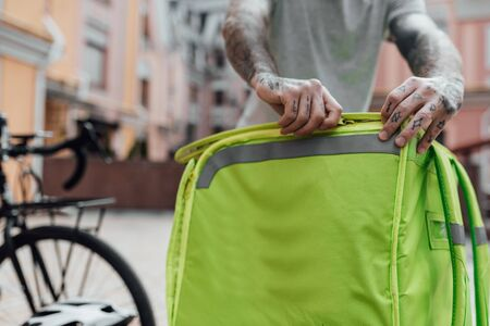 Fast, Fresh, Instant. Close up of delivery man closing thermo bag or backpack to be ready to go, standing outdoors with bike. Courier, delivery service concept
