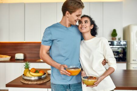 Beware what you eat. Happy couple, vegetarians looking at each other while standing in the kitchen. Young man and woman holding smoothie bowls. Vegetarianism, healthy food, diet, stay home concept 写真素材