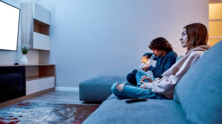 Side view of young caucasian guy lighting cannabis in the bowl of glass water pipe or bong while playing video games with friend, they sitting on the couch at home
