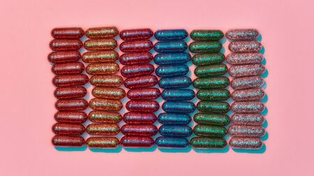 Creative concept with many colorful glitter pills lying in rows isolated on pastel pink background. Minimal style, art concept