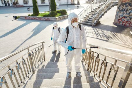 Protecting Lives. Sanitization, cleaning and disinfection of the city due to the emergence of the Covid19 virus. Specialized team in protective suits and masks at work