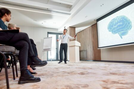Making a Difference. Full-length shot of asian male speaker in suit with headset and laser pointer giving a talk at corporate business meeting