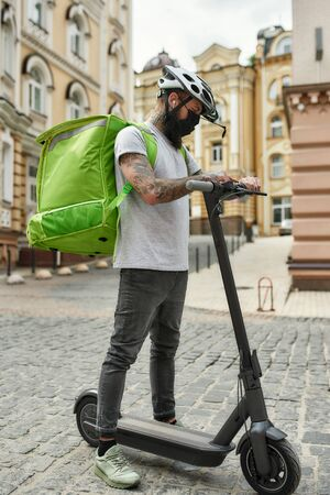 Performance on time. Brutal bearded delivery man with thermo backpack wearing mask due to the emergence of the Covid19 virus, checking the time while riding a scooter. Courier, lockdown concept