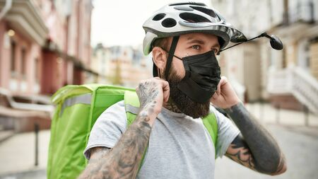 Brutal bearded delivery man in helmet wearing mask due to the emergence of the Covid19 virus, ready to work, riding a bicycle. Focus on a courier, delivery service, lockdown concept. Horizontal shot