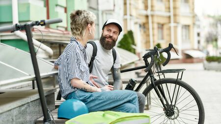 Two cheerful couriers, young man and woman sitting on the bench and talking outdoors while delivering food and products, using scooter and bike Foto de archivo