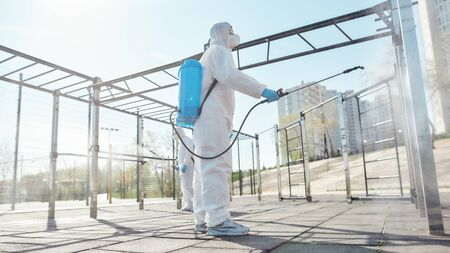 It needs to be sanitized. Sanitization, cleaning and disinfection of the city due to the emergence of the Covid19 virus. Man in protective suit and mask at work near sports ground