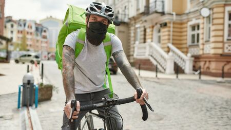Brutal bearded delivery man in helmet wearing mask due to the emergence of the Covid19 virus, riding a bicycle, while delivering food. Courier, delivery service, lockdown concept. Horizontal shot