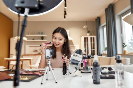 The Beauty Authority. Asian female blogger applying makeup while recording a tutorial video for her beauty blog using camera at home