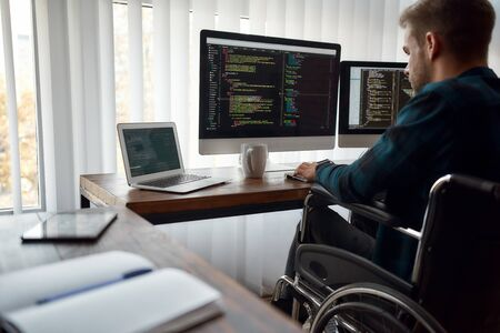 I can work with any code. Concentrated male web developer in a wheelchair writing program code on multiple computer screens while sitting at his workplace in the modern office