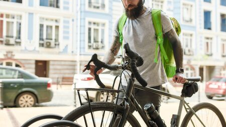 Make it accordingly. Cropped shot of bearded delivery man with thermo bag or backpack parking his bike, delivering food. Courier, delivery service concept Stok Fotoğraf