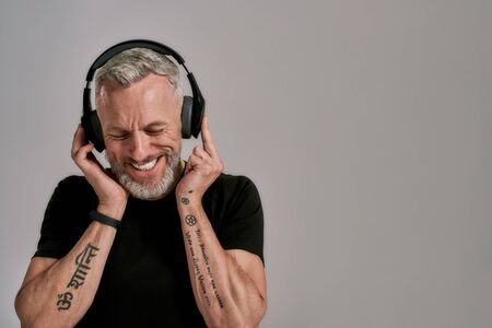 Enjoy the beat. Middle aged muscular man in black t shirt and headphones smiling while listening to music, posing in studio over grey background