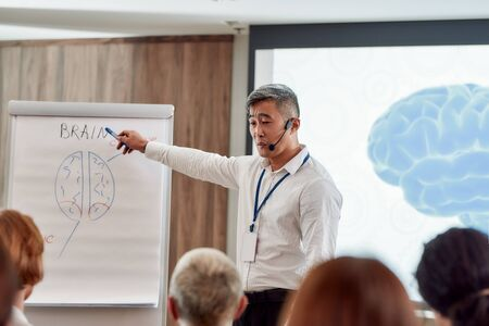 Engaging minds, empowering success. Asian male speaker in suit with headset and laser pointer giving a talk at corporate business meeting