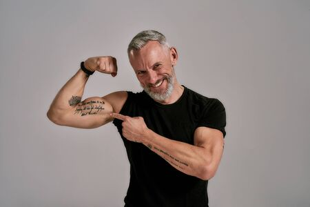 Look at this. Smiling middle aged muscular man in black t shirt showing his biceps, tattoos while posing in studio over grey background