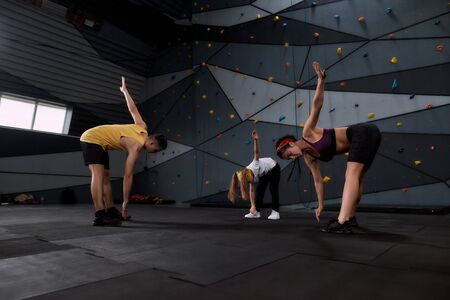 Full length shot of woman and little girl going to climb, male instructor helping them to warm up against artificial training climbing wall. Concept of sport life and rock climbing 스톡 콘텐츠