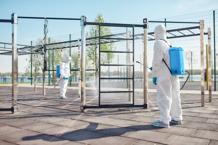 Quality and Safety. Sanitization, cleaning and disinfection of the city due to the emergence of the Covid19 virus. Specialized team in protective suits and masks at work near sports ground 写真素材