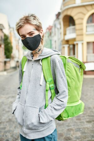 Young woman with thermo backpack wearing mask due to the emergence of the Covid19 virus, walking along the street, delivering food. Courier, delivery service, lockdown concept