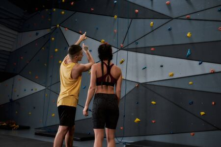 Altitude, Not Attitude. Active young woman in sportswear going to climb, male instructor helping her, standing against artificial training climbing wall. Concept of sport life and rock climbing