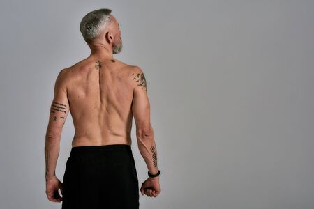 Half middle aged muscular man looking aside, showing his back, body while posing in studio over grey background