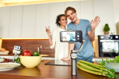 Happy couple, vegetarians smiling, recording a video on smartphone while going to prepare a healthy meal in the kitchen together. Vegetarianism, healthy food, blog concept