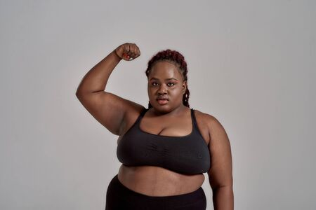My body. Plump, plus size african american woman in black sportswear looking at camera, showing strong arm in studio over grey background. Concept of sport, healthy lifestyle, body positive, equality